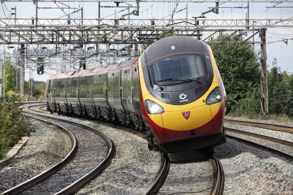 A Pendolino tilting train, heading to London, tilts as it rounds a bend on the West Coast main line near Wolverton station, Bucks